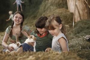 Kinder spielen im Heu bei Ferien auf dem Bauernhof